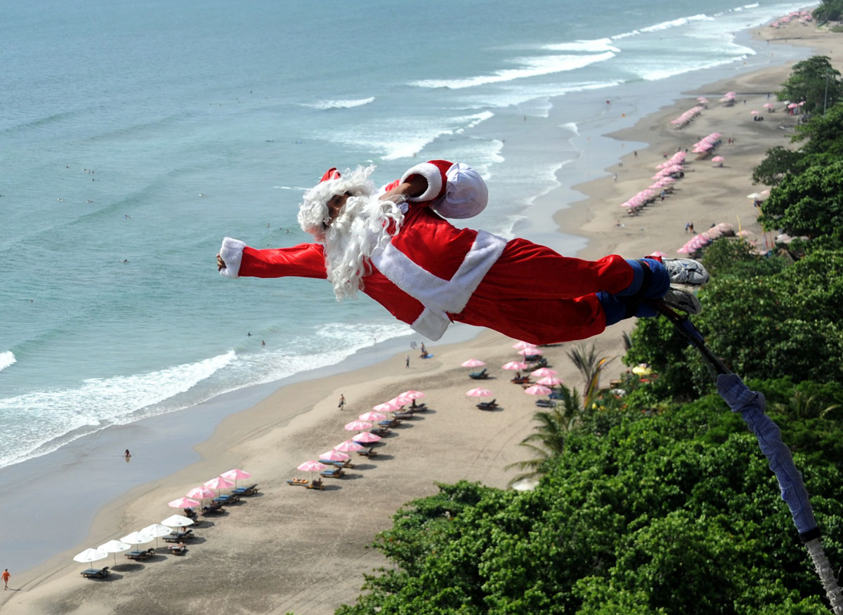 A bungee jumper dressed as Santa Claus leaps from a platform above Kuta  beach, Denpasar on Indonesia's resort island of Bali on December 2, 2011.  AFP PHOTO / SONNY TUMBELAKA (Photo credit should read SONNY TUMBELAKA/AFP/Getty Images) ORG XMIT: